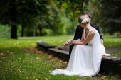 Bride And Groom Are Sitting In Autumn Park