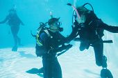 Friends on scuba training submerged in swimming pool on their holidays