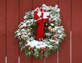 foto of red barn  - A snow covered Christmas wreath hanging on a red barn presents the image of a country Christmas celebration - JPG