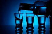 image of shot glasses  - Studio shot Vodka poured into a glass with glasses lit with blue backlight - JPG