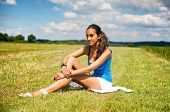 Tanned beautiful slender young teenage girl sitting on the grass in a green field enjoying the summe