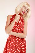 Thoughtful Girl In Blond Wig And Retro Red Dress Winking. Pinup.