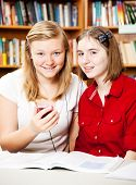 Girls using a smart phone to listen in the library.