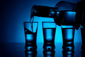 picture of shot glasses  - Studio shot Vodka poured into a glass with glasses lit with blue backlight - JPG