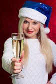 Girl In Santa Hat In White Sweater Smiling With A Glass Of Champagne