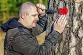 Man holding knife and fabric heart near the tree