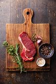 Raw Fresh Meat Ribeye Steak Entrecote And Seasonings On Cutting Board On Dark Wooden Background