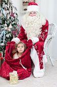 Little girl sits in Saint Nicolas bag