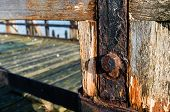 stock photo of neglect  - Part of a neglected wooden jetty with rusted iron from close - JPG