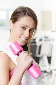 Smiling Young Woman Weightlifting At The Gym