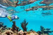 Teenage boy swimming underwater in shallow turquoise water at coral reef