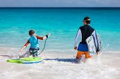 Father and son running towards ocean with boogie boards