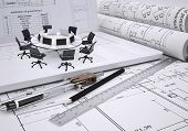 Round table, compasses, scrolls, architectural drawing and laptop