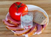 bread, meat, tomatoes and a glass of vodka