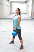 Beautiful sporty hispanic woman in blue  lifting blue kettlebell  for dead lift, outdoors