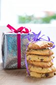 Stacks of chocolate chip cookie tied up next to a wrapped up Christmas present.
