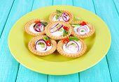 Tartlets with greens and vegetables with sauce on plate on table