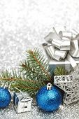 Christmas fir tree branch and decoration on silver glitter background