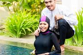 Muslim woman or girl in swimming pool in tropical garden wearing Burkini halal swimwear greeting her husband