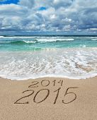 stock photo of new year 2014  - Happy New Year 2015 wash away year 2014 concept on sea sand beach - JPG