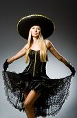 Woman wearing black sombrero dancing