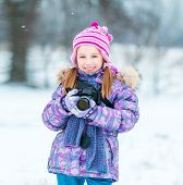 little girl with a camera in the winter park