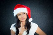 image of fussy  - Closeup portrait of a cute christmas woman with a red santa claus hat white dress finger on chin confused thinking what to shop for the holiday season - JPG