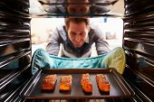 image of picking tray  - Man Taking Cooked Tray Of Salmon Fillets Out Of The Oven - JPG
