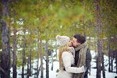 Amorous guy and girl kissing in natural environment