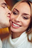 Amorous guy kissing beautiful girl on cheek