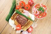 meat food : roasted fillet mignon on bread in white bowl garnished with tomatoes salad on wooden table