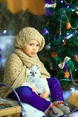 pic of knitted cap  - the girl in lilac jeans in a knitted cap and with a knitted scarf sits on a sledge near a Christmas fir - JPG