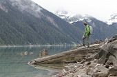 Man standing on a cliff looking at mountain lake
