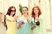 tourism, travel, leisure, holidays and friendship concept - smiling teenage girls with city guide and camera showing thumbs up outdoors