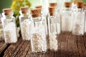 Homeopathic lactose sugar globules in glass bottles