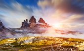 Great foggy view of the National Park Tre Cime di Lavaredo with rifugio Locatelli. Dolomites, South Tyrol. Location Auronzo, Italy, Europe. Dramatic cloudy sky. Beauty world. Tilt shift blur effect.