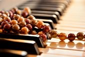 Pearl necklace on piano keyboard.