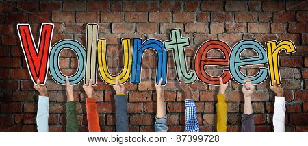Group of Hands Holding Letter Volunteer