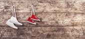 image of wooden fence  - Two pairs of sports shoes hang on a nail on a wooden fence background - JPG
