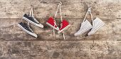 picture of wooden fence  - Three pairs of sports shoes hang on a nail on a wooden fence background - JPG
