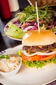 image of bread rolls  - Tasty traditional cheeseburger with a ground beef patty topped with melted cheese and served with onion rings tomato and curly leaf lettuce on a round white bread roll close up view - JPG