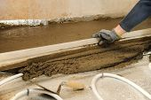 foto of concrete pouring  - Man aligns fresh concrete with a ruler and a trowel - JPG