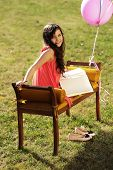 stock photo of sketch book  - Cute little girl on the bench holding a sketch - JPG