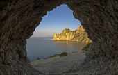 stock photo of grotto  - View of the coastal cliffs from a small grotto in the rock - JPG