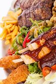 picture of leafy  - Wholesome platter of mixed meats including grilled steak crispy crumbed chicken and beef on a bed of fresh leafy green mixed salad served with French fries and chutney or BBQ sauce in a dish