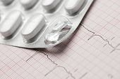 stock photo of electrocardiogram  - Forefront of a white medicine pills in blister pack and electrocardiogram - JPG