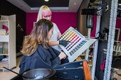 picture of hair dye  - Beautiful young woman looking with hairdresser a hair dye palette to change her hair color - JPG
