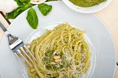 foto of pine nut  - Italian traditional basil pesto pasta ingredients parmesan cheese pine nuts extra virgin olive oil garlic on a rustic table - JPG