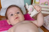 picture of diaper change  - Closeup of adorable baby lying playing with a toy rubber for children after the change of diaper - JPG
