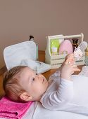 stock photo of diaper change  - Adorable baby lying playing with a children comb after the change of diaper - JPG